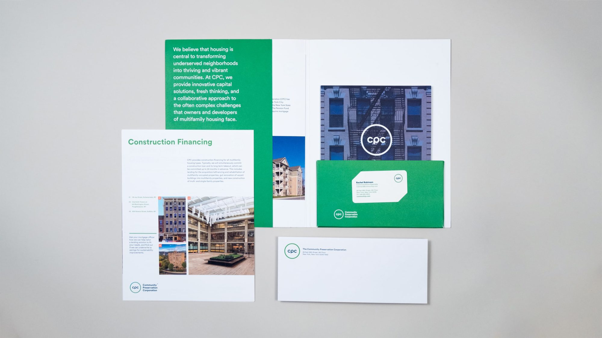 Full suite of brand materials laid out including a custom folder, capabilities brochure, one sheet, business envelope, and business card