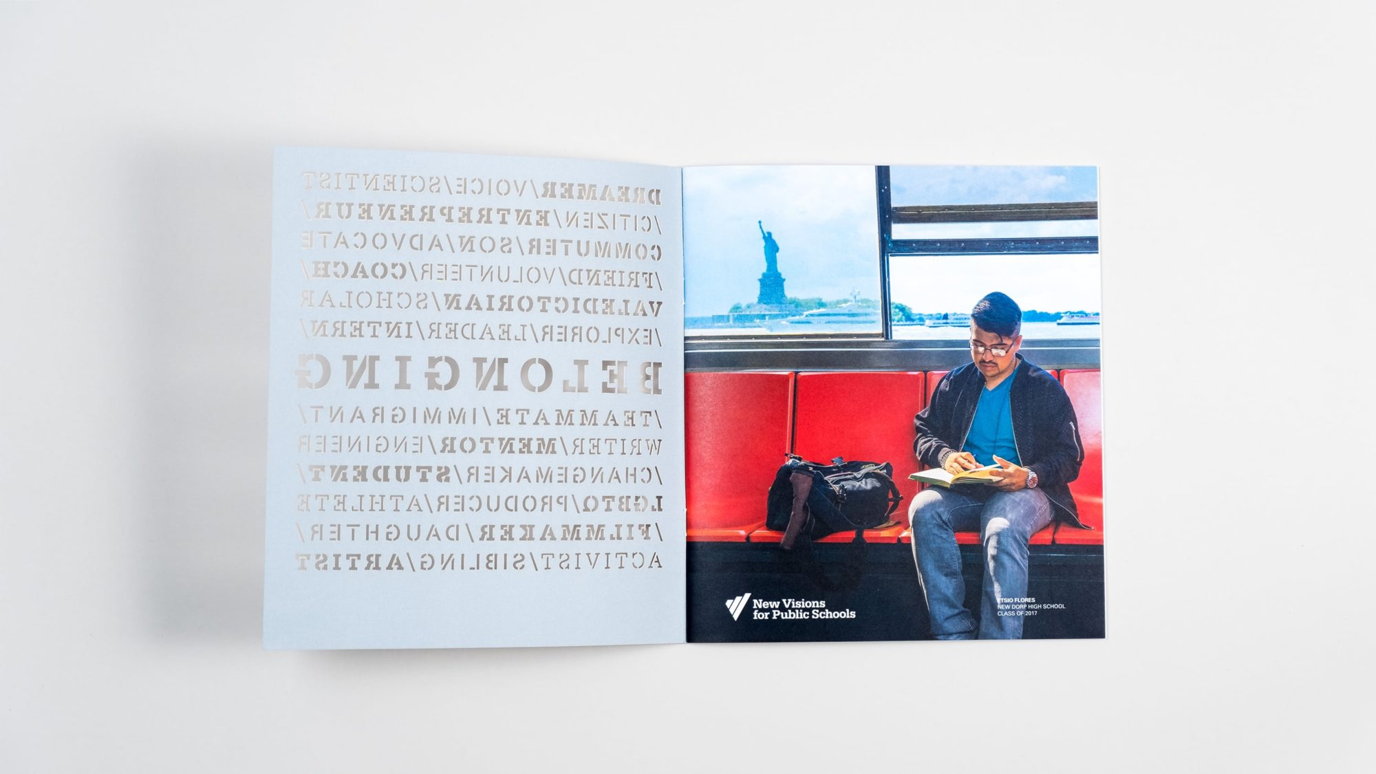 Inside front cover and opening page of annual report revealing photograph of New Visions student reading a book on the subway